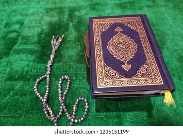 Al-quran and rosady tasbih bead on praying mat. Muslim and islam image concept