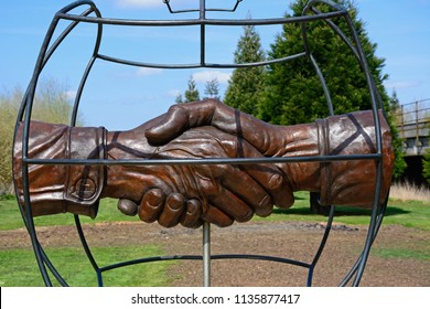 ALREWAS, UK - APRIL 18, 2018 - Christmas Truce Memorial showing soldiers handshake within a globe, National Memorial Arboretum, Alrewas, Staffordshire, England, UK, Western Europe, April 18, 2018.