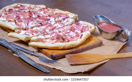 Alsatian tart flambé or Flammkuchen with bacon and onions on a dark table.