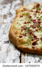 Alsatian tarte flambe with bacon and onions on a wooden background. Flammkuchen, Alsace thin pizza.