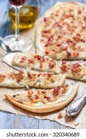 Alsatian tarte flambe with bacon and onions on a wooden background