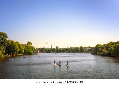 Alster Lake in Hamburg with people on  paddle boards and the TV tower in the background