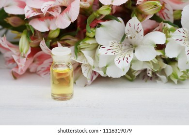 Alstroemeria flowers oil (tincture, extract). Alstroemeria. Bouquet of flowers Alstroemeria on white wooded background
