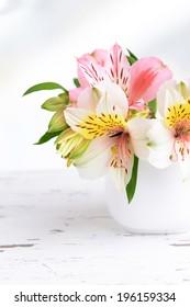 Alstroemeria flowers in vase on table on light background