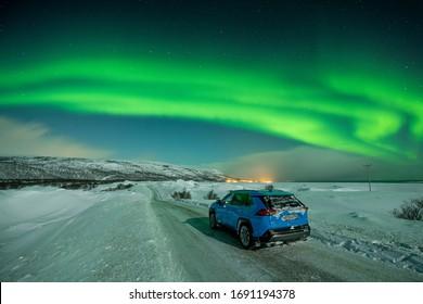 Alta, Norway - Jan 4, 2020: Blue Toyota Rav4 Hybrid standing near snow road under aurora Notheren Light
