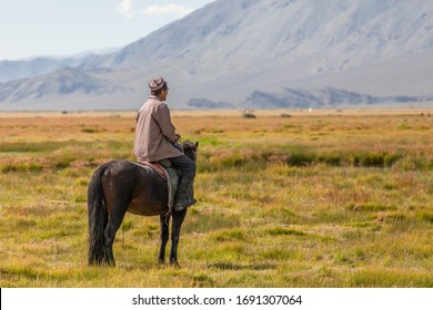 Altai, Mongolia - June 14, 2017: Nomad with his faithful horse in the steppes of Mongolia. Horseback in Mongolia. Mongolian valley view
