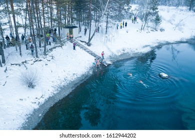 Altai, Russia - 03.01.2020: Aerial view of people bathing in an icy and cold blue lake with snow in the winter in the mountains during wellness and baptism. People walrus and health care.