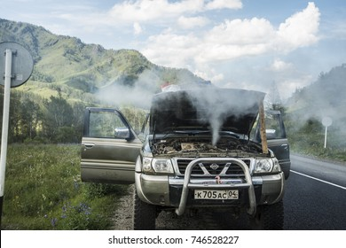 ALTAI, RUSSIA -AUGUST 04,2017: Overheated SUV car stand against summer mountain. smokey car engine shows signs of lack of maintenance.broken down car with smoke or steam from hose leak smoke