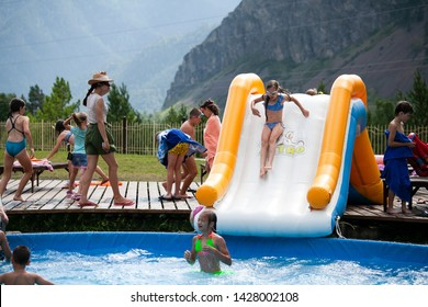 Altai, Russia – August 08, 2018:The company of children and teenagers in summer clothes and swimsuits rolls off an inflatable slide and basks in the pool at the summer international camp in the Chemal