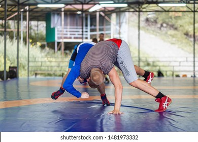 Altai, Russia – August 16, 2019:  Two young men in   wrestling tights are wrestlng and making a suplex wrestling on a blue wrestling carpet in the gym. Open training and summer sports camps