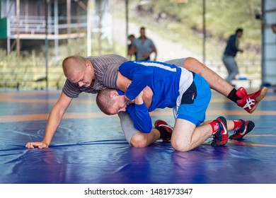 Altai, Russia – August 16, 2019:  Two strong men in   sporting clothes are wrestlng on a blue wrestling carpet in the gym. Open training and summer sports camps
