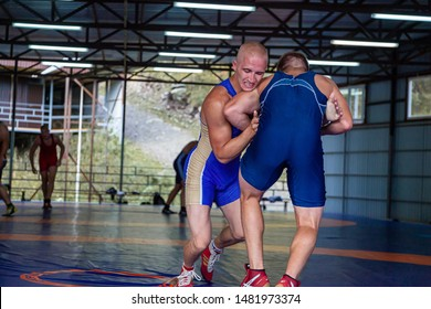 Altai, Russia – August 16, 2019:  Two young men in   wrestling tights are wrestlng and making a hip throw on a blue wrestling carpet in the gym. Open training and summer sports camps