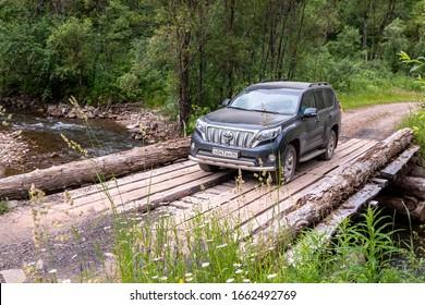 Altai, Russia - Jun 2019: Car on the old wooden bridge over a mountain river in the taiga. Katun river. Gorny Altai Republic, Siberia, Russia