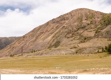 Altai steppe on the background of the mountain range. Kurai steppe, mountain valley at Mongolia border. Panorama.  Kosh-Agachsky District, Altai, Siberia, Russia