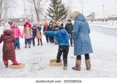Altai Territory, RUSSIA - February 15, 2018: Shrovetide, children are entertained on the street. Russian folk games. Entertainment for children at Shrovetide.