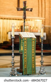 Altar in the church, book, cross and candles.