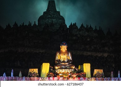 Altar with golden colored buddha-statue and offerings, ancient stupa in background, night / The celebration of the Buddha day, Vesak - Vesakha - Waisak at Borobudur, Indonesia