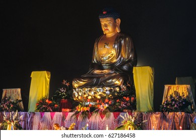 Altar with golden colored buddha-statue and offerings, ancient stupa in background, night, close up / The celebration of the Buddha day, Vesak - Vesakha - Waisak at Borobudur, Indonesia