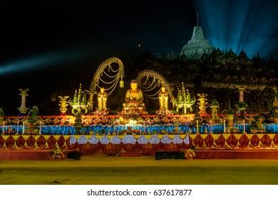 Altar with golden colored buddha-statue and offerings, night / The celebration of the Buddha day, Vesak - Vesakha - Waisak at Borobudur, Indonesia, 2017