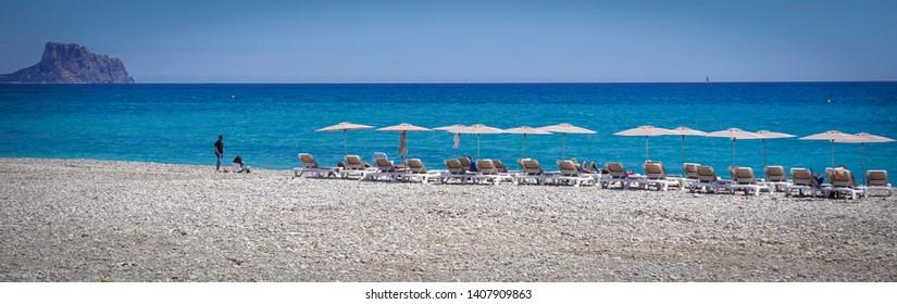 ALTEA, SPAIN - MAY 26, 2019: Beautiful Altea beach with chairs and sunbathing tourists