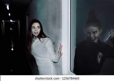 alter ego. reflection in window or mirror. bloody killer woman with sharp knife against scary young girl in dark long corridor. happy halloween. another self