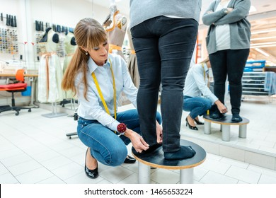 Alterations tailor measuring trousers on a customer, close-up