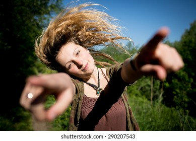 Alternative beautiful girl whipping her hair sideways while pointing fingers outward