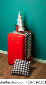 Alternative Christmas spot. Vintage old red fridge with holiday ornaments on top. Two silver trees and matching black and white pattern in cushion. Wooden floor and green wall on the back.