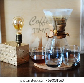 Alternative coffee brewing in the filter. Glass beakers. Table lamp with Edison bulb. Cozy still Life