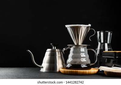 Alternative coffee brewing method,pure over,glass teapot on wooden tray with freshly brewed coffee on dark background.