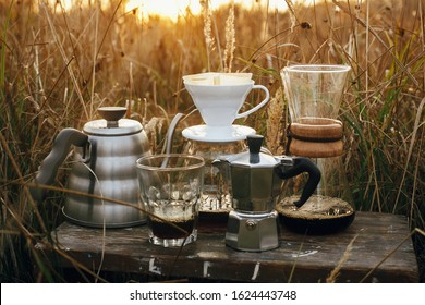 Alternative coffee brewing outdoors in travel. Steel kettle, hot coffee in cup, coffee dripper,  geyser maker, glass flask with filter on background of sunny warm light in rural herbs.