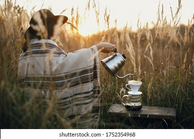 Alternative coffee brewing in travel. Hipster woman in hat pouring hot water into coffee in filter in pour over on glass flask on background of sunny warm light in rural herbs.