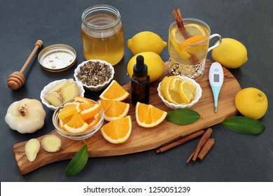 Alternative cold and flu remedy with thermometer, eucalyptus oil, fresh ginger, orange and lemon fruit, cinnamon sticks and honey with medicinal hot drink on slate background.