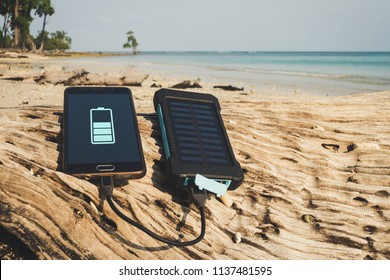 Alternative energy source. battery is charged by solar energy. Charging mobile devices in the wild. island beach. Powerbank charges the phone on the background of palm trees and sandy beach