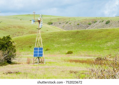 Alternative Energy Sources Modern Solar Panel on Rusty Vintage Windmills in Rolling Hills of San Simeon, California Juxtaposition..
