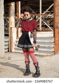 Alternative girl on an abandoned construction background taking off hipster round glasses and holds white penny skate board