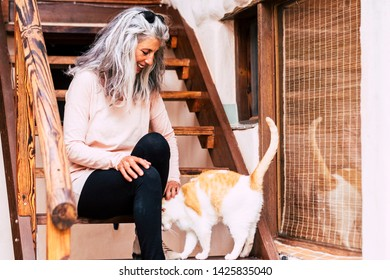 Alternative grey white hair young woman stay sit down outside rural wooden home and play with a nomad cat - love for animals and unusual diversity people concept