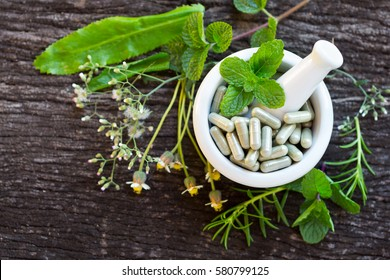 Alternative health care fresh herbal plant and herbal capsule in white Mortar Grinder drugs on old rustic wooden background over green bokeh background
