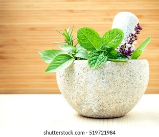Alternative health care and herbal medicine .Fresh herbs with mortar and pestle on wooden background. Various herbs rosemary ,sage ,sweet basil leaves and  green mint branch.