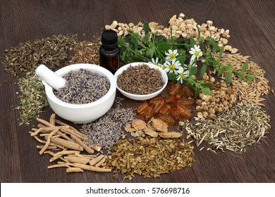 Alternative herbal medicine for sleeping and anxiety disorders with essential oil bottle and mortar with pestle on oak background.