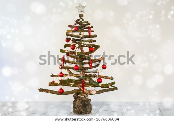 Alternative homemade Christmas tree made of rustic raw wood branches, with fairy lights and red baubles, sustainable craft for eco friendly holidays, copy space, selected focus, narrow depth of field