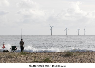 Alternative lifestyle and green living fisherman. Sustainable resource fishing. Wind power and renewable wave energy represented with offshore windfarm turbines and sea waves.