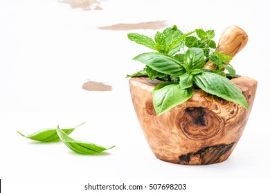 Alternative medicine fresh herbs in the wooden mortar . Food ingredients and seasoning basil, peppermint , dill and green mint  in a wooden mortar set up on white wooden background with copy space.