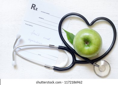 Alternative medicine healthy  sign concept with stethoscope heart and green apple on white background
