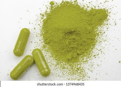 Alternative medicine, herbal pain management and opioid withdrawal treatment concept theme with a pile of green kratom powder and capsules or pills isolated on white background
