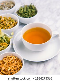 Alternative Medicine. Herbal Therapy. Cup of infusion and dried healing herbs. White background.Selective focus.
