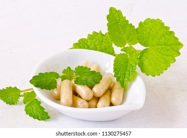 Alternative Medicine. Herbal Therapy. Melissa or lemon balm capsules. White background.