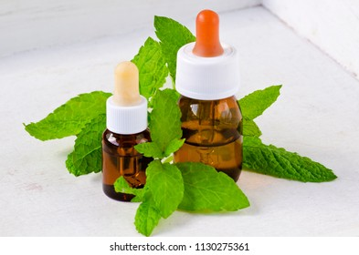 Alternative Medicine. Herbal Therapy. Mint essential oil. White background.