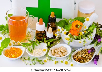 Alternative Medicine. Herbal Therapy. Rosemary, mint, chamomile, thyme, melissa, lavender and calendula. First aid box in background.