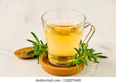 Alternative Medicine. Herbal Therapy. Rosemary infusion in glass cup. White background.